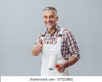 Cheerful painter and decorator giving a thumbs up, he is holding a paint roller