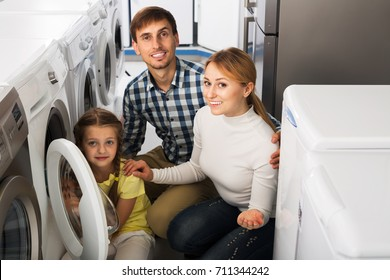 Cheerful parents with daughter choosing washing machine in home appliance store. Focus on woman