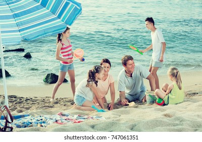 Cheerful parents with four children in different ages playing with beach toys on sunny summer day