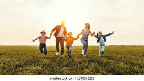Cheerful parents with kids smiling and running on green grass while having fun in meadow during sunset