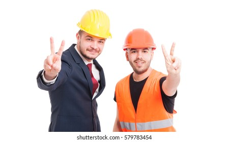 Cheerful partners doing victory gesture on white studio background