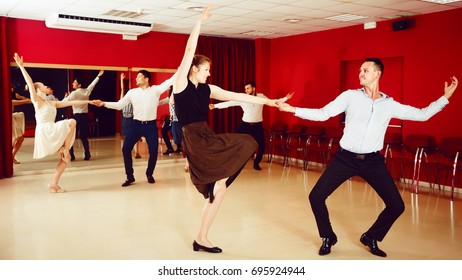 Cheerful people dancing lindy hop in pairs in dance hall