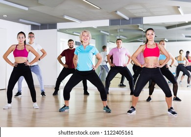 Cheerful people of different ages studying zumba dance elements in dancing class
