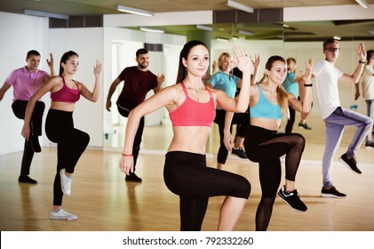 Cheerful people of different ages studying zumba dance elements in dancing hall