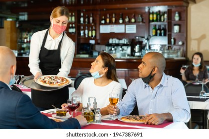 Cheerful people in protective masks having friendly meeting in pizzeria, young waitress in mask serving guests. Concept of reopening restaurants after quarantine due to coronavirus