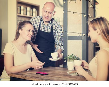 cheerful people spending time in cafe for cup of coffee