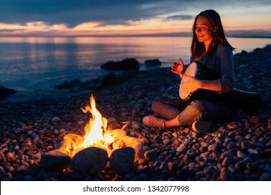 cheerful percussionist girl playing djembe sitting on the beach by the fire at sunset.
