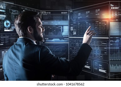 Cheerful person. Handsome young positive programmer feeling happy and gently touching the screen of his futuristic device while finishing his working day