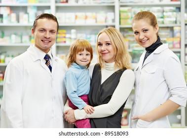 Cheerful pharmacist chemist woman giving vitamins to child girl in pharmacy drugstore