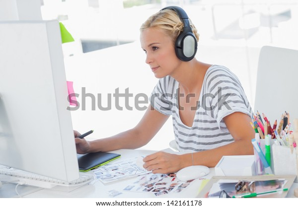 Cheerful photo editor working with graphics tablet at her desk