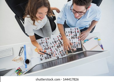 Cheerful photo editors working on their computer with contact sheets