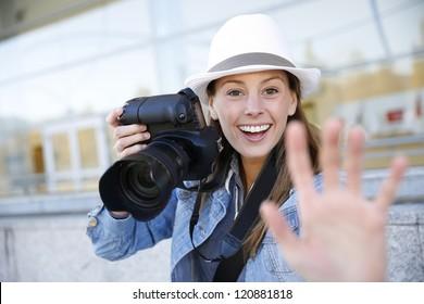 Cheerful photographer showing hand towards camera