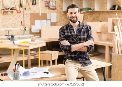 Cheerful pleasant bearded joiner is resting at work