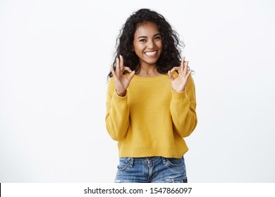 Cheerful pleased dark-skinned girl student in yellow sweater smiling with approval and delight, show okay good gesture, rate excellent promo, recommend great app, looking satisfied, white background