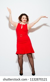 Cheerful plump female in bright reed dress and high-heels dancing and gesturing with hands while standing on white background