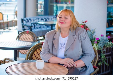 Cheerful plump lady is sitting at the table in cafe and drinking tea. Young pretty funny woman having lunch at a cafe on the street