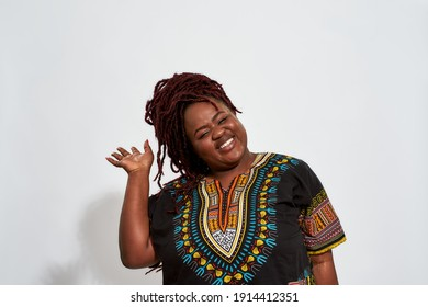 Cheerful plump young african american woman waving to camera and smiling while standing on white background. Emotions and feelings concept
