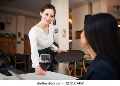 Cheerful and polite young waitress look at customer and smile. She put glass of wine on table. Female customer sit at table and smile to waitress.