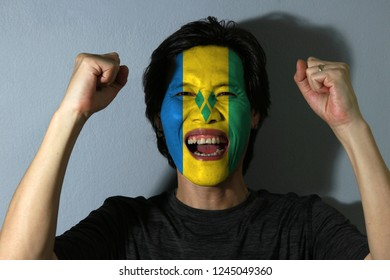 Cheerful portrait of a man with the flag of Saint Vincent painted on his face on grey background. The concept of sport or nationalism. blue gold and green with three green diamonds.