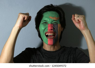 Cheerful portrait of a man with the flag of Zambia painted on his face on grey background. The concept of sport or nationalism.