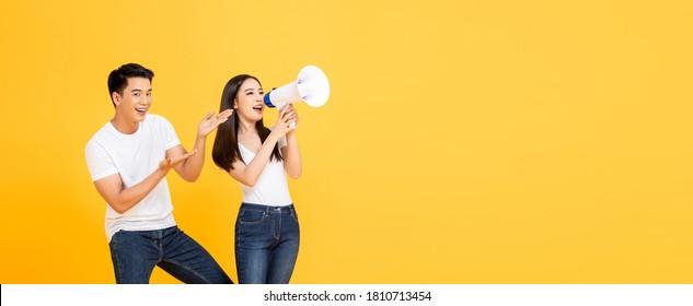 Fröhliches Bannerporträt von lächelndem junges asiatisches Paar, das Ankündigung macht und auf isoliertem, gelbem Hintergrund präsentiert