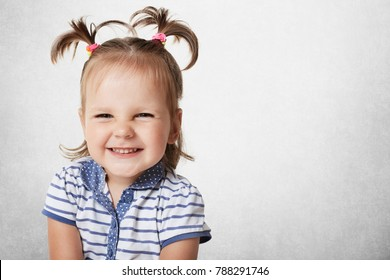 Cheerful positive adorable small child with two pony tails, dressed in striped t shirt, expresses pleasant emotions, being glad to recieve new toy from parents, isolated on white wall, copy space