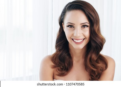 Cheerful positive beautiful bride with wavy hair and perfect makeup excited about wedding looking at camera in light room
