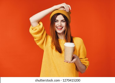 Cheerful positive caffeine woman, woman in a yellow sweater and a cap with coffee in her hands posing on a yellow isolated background
