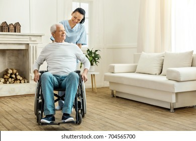 Cheerful positive caregiver moving a wheelchair