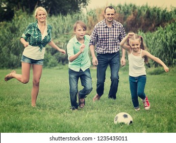 Cheerful positive children and parents running with ball at sunny day