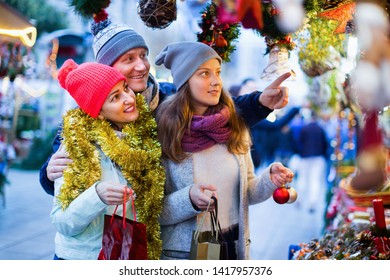 Cheerful positive family of three at Christmas market. Selective focus