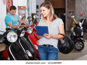 Cheerful positive female is shopping and choosing new motobike in moto store.