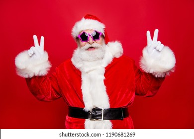 Cheerful positive funky aged stylish mature Santa in headwear costume glasses with white beard laugh fooling around show v-sign isolated on christmastime noel vivid red background