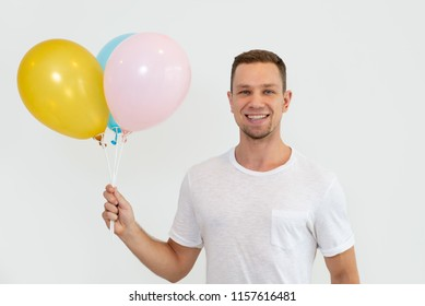 Cheerful positive man with stubble holding bunch of balloons and looking at camera. Happy handsome young guy selling helium balloons. Birthday concept