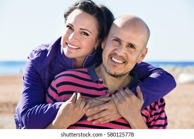 Cheerful positive mature couple gladly hugging each other and enjoying the beach