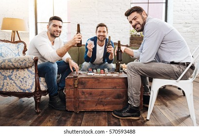 Cheerful positive men playing card games