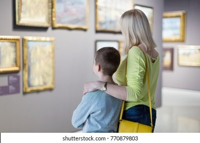 Cheerful positive mother and son regarding paintings in halls of museum
