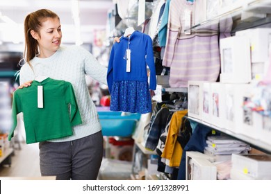Cheerful positive pregnant woman is choosing baby clothes in the shop.