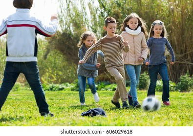 Cheerful positive smiling kids playing football outdoors in sunny day