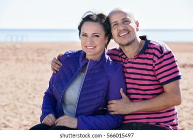 Cheerful positive smiling mature couple gladly hugging each other and enjoying the beach