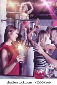 Cheerful positive smiling woman and man joying in the night club with drinks in the hand