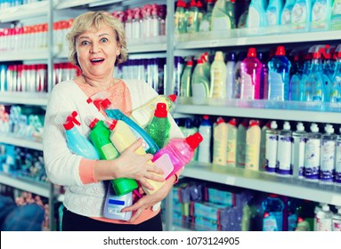 Cheerful positive  woman consumer with household chemical products for washing indoors