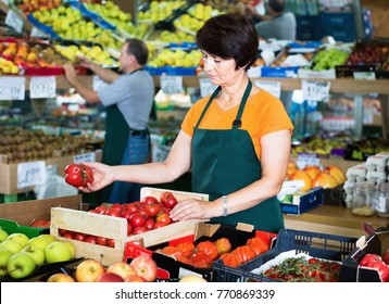 Cheerful positive woman seller is demonstraiting red tomatos in the store.