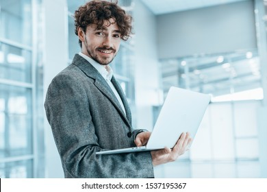 Cheerful positive young businessman stand in room and pose. Look straight and smile. Hold laptop in hands and type on keyboard. Expert, executive or professional worker. Work remote. Alone in room
