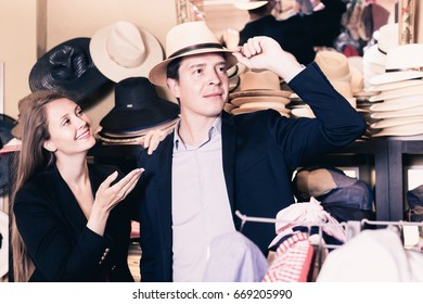 Cheerful positive young girl and male try on modern hats at the boutique