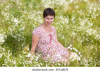 Cheerful pregnant woman sitting in chamomile background