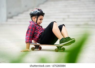 Cheerful preschool boy sitting on skateboard