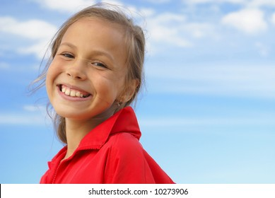 Cheerful preteen girl on blue sky background