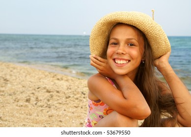 Cheerful preteen girl in straw hat enjoying sun-bath on sea beach