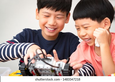 Cheerful preteen / teenage Asian brother assembles and shows his robotics project to cute little boy. Two brothers laugh, smile, have fun. Family Activity, Quality happy time, Brotherhood Bonding.